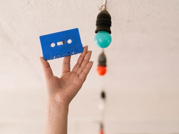 Persona con cinta de cassette azul cerca de bombillas multicolores Foto gratis
