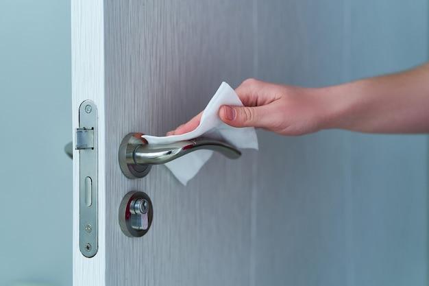La persona desinfecta y limpia la manija de la puerta con toallitas húmedas antibacterianas para proteger contra el brote de coronavirus Foto Premium