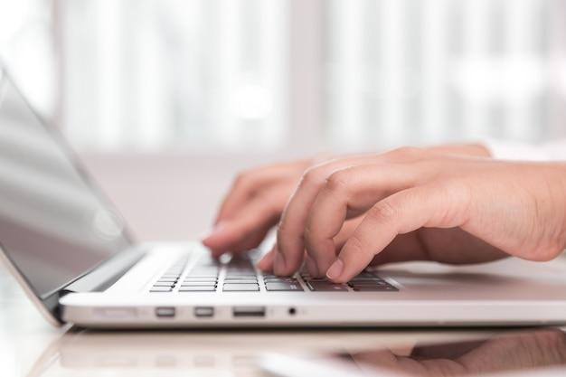 Persona escribiendo en un ordenador portátil Foto gratis