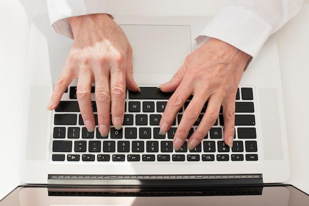 Persona escribiendo en la vista superior del portátil Foto gratis