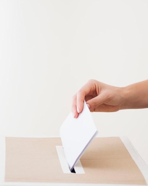 Persona de lado poniendo papeleta en la casilla de elecciones Foto gratis
