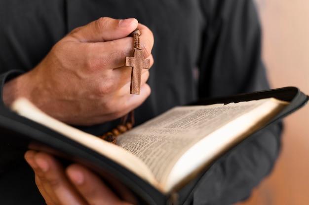 Persona con libro sagrado y rosario Foto gratis