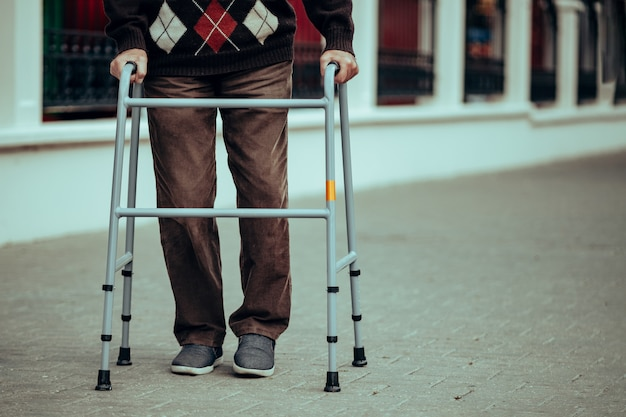 Una persona mayor usa un andador para caminar por la ciudad. apoyo ortopédico durante lesiones en las piernas y ayuda para personas con discapacidad. Foto Premium