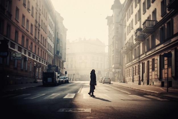 Persona en medio de las calles de poznan rodeada de viejos edificios capturados en polonia Foto gratis