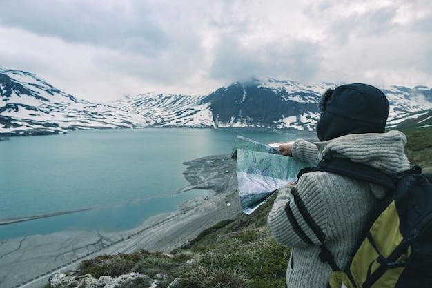Una persona mirando el mapa de trekking, cielo dramático al atardecer, lago y montañas nevadas, sensación de frío nórdico Foto Premium