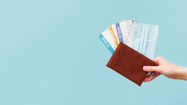 Persona con pasajes de avión y pasaporte con espacio de copia Foto gratis