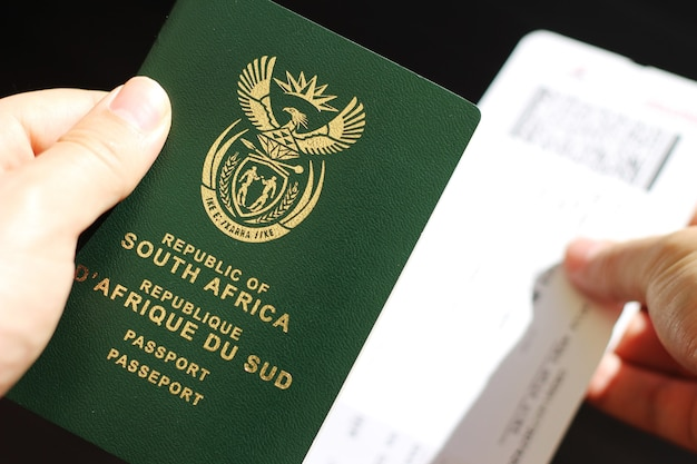 Persona con pasaporte de la república de sudáfrica y billete de avión Foto gratis