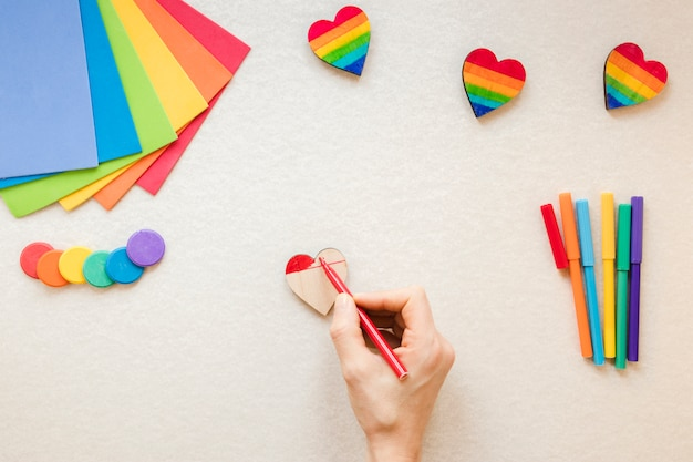 Persona pintando corazón de arcoiris con rotulador rojo Foto gratis