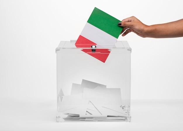 Persona poniendo tarjeta de bandera de italia en urna Foto gratis