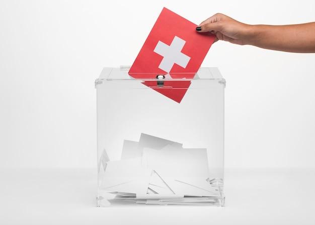 Persona poniendo tarjeta de bandera de suiza en urna Foto gratis