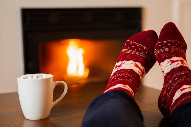 Persona de primer plano con bebida de malvavisco y calcetines acogedores Foto gratis