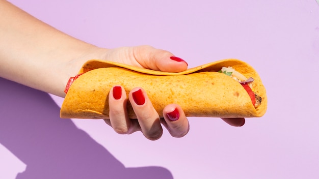 Persona de primer plano con burrito y fondo morado Foto gratis