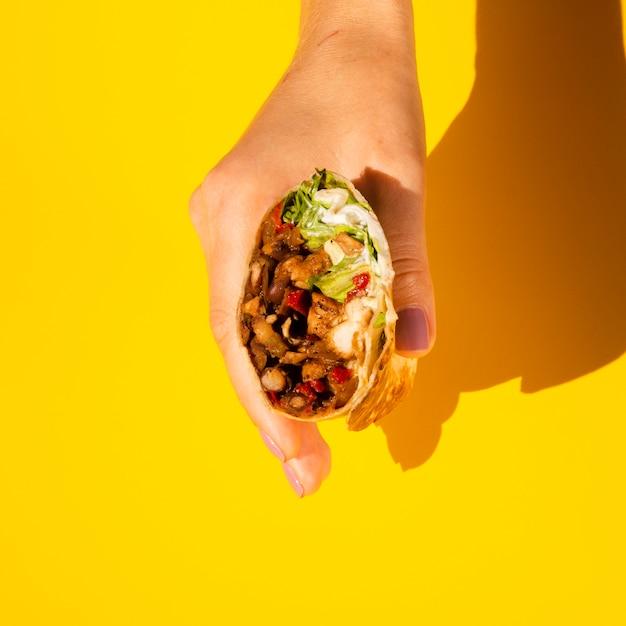 Persona de primer plano con sabroso burrito Foto gratis