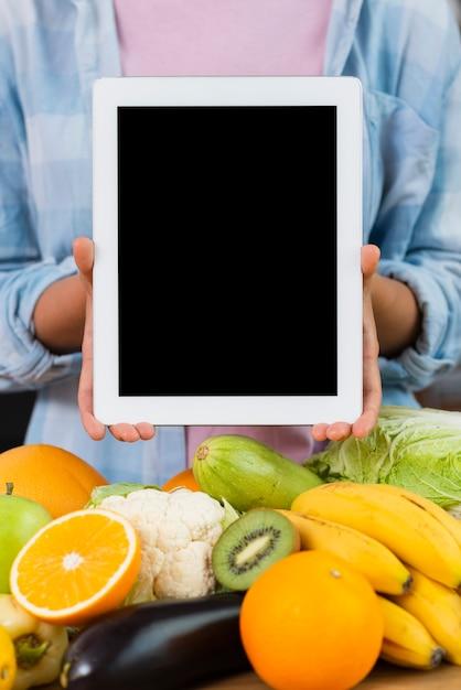 Persona de primer plano sosteniendo maqueta de tableta Foto gratis