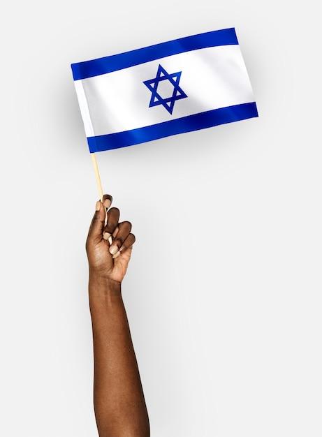 Persona que agita la bandera del estado de israel Foto gratis