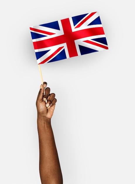 Persona que agita la bandera del reino unido de gran bretaña e irlanda del norte Foto gratis