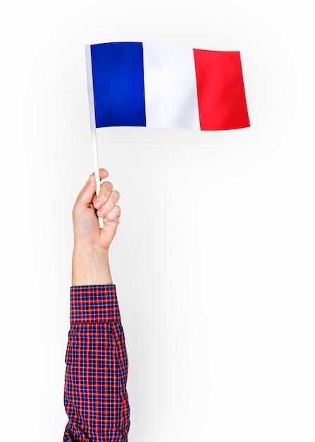 Persona que agita la bandera de la república francesa Foto gratis