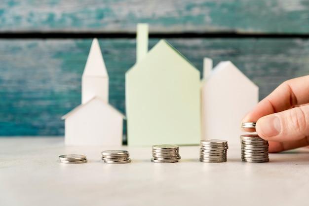 Una persona que arregla el aumento de monedas frente a casas de papel en superficie blanca Foto gratis