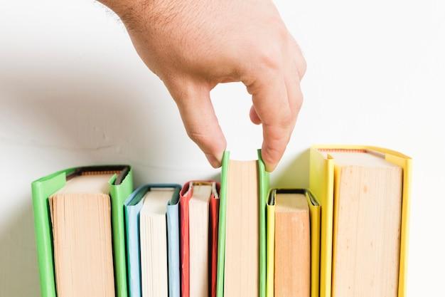 Persona que elige el libro del estante Foto gratis
