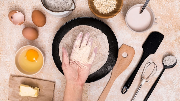 Una persona que muestra la harina en el plato con ingredientes de pan en el telón de fondo Foto gratis