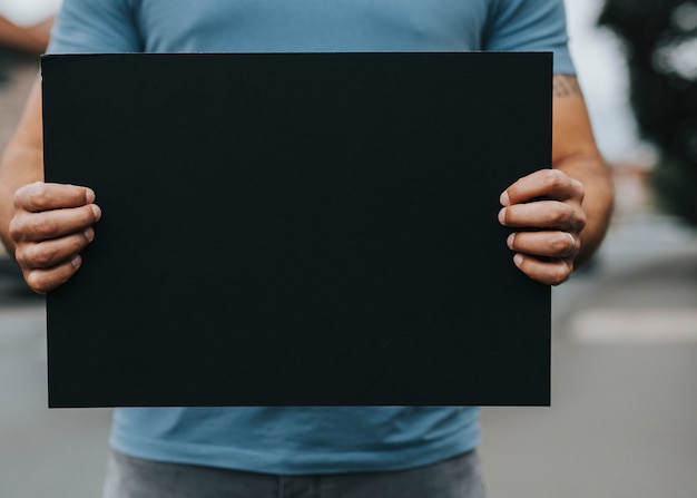 Persona que muestra un tablero en blanco para apoyar un movimiento. Foto Premium