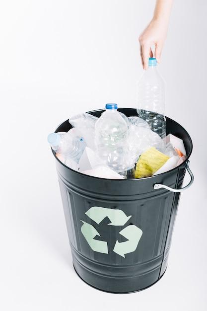 Una persona que pone la basura en el cubo de reciclaje contra el fondo blanco Foto gratis