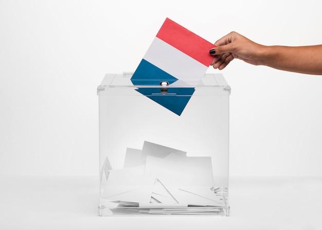 Persona que pone la tarjeta de la bandera de francia en la urna Foto gratis
