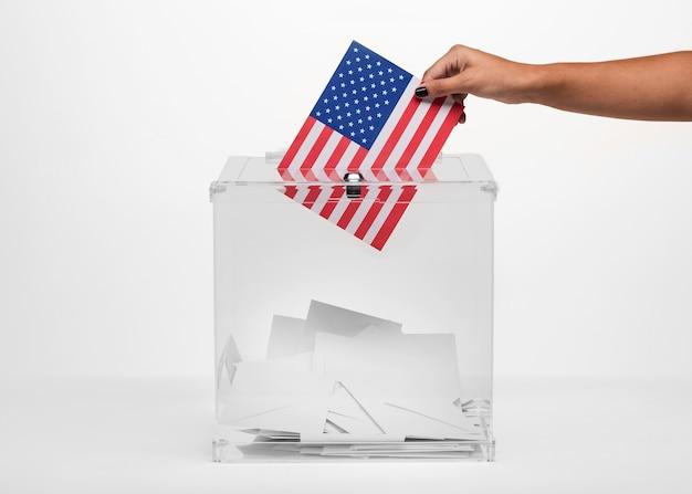 Persona que pone un voto estadounidense en urna Foto gratis