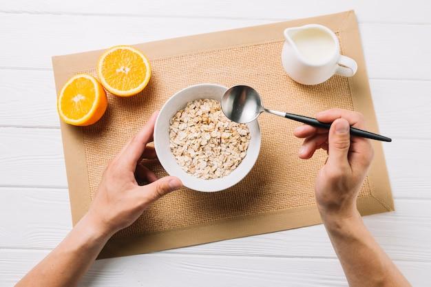 Persona que tiene harina de avena; mitad de naranja y leche en manteca de yute sobre superficie blanca Foto gratis