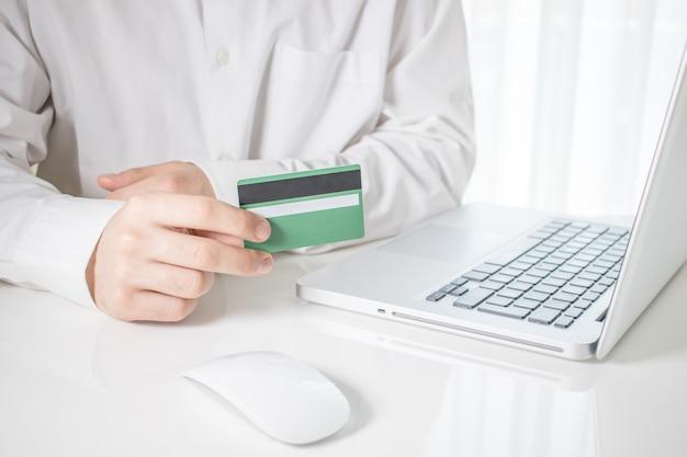 Persona que tiene una tarjeta de crédito verde con una computadora portátil y un mouse de computadora sobre una mesa blanca Foto gratis