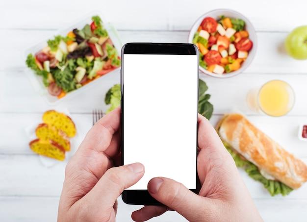 Persona que toma una foto de deliciosa merienda saludable Foto gratis
