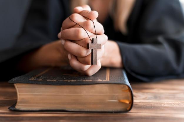 Persona rezando con cruz y libro sagrado Foto gratis