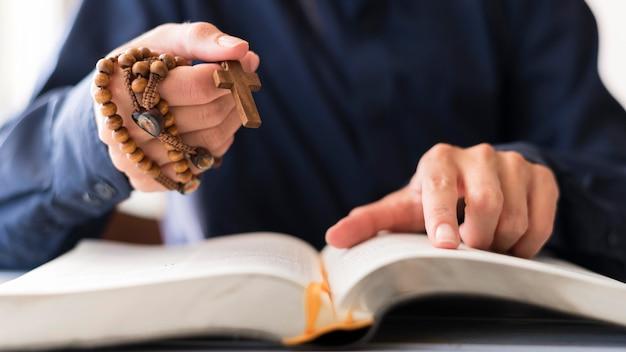 Persona con rosario con cruz y rezando Foto gratis