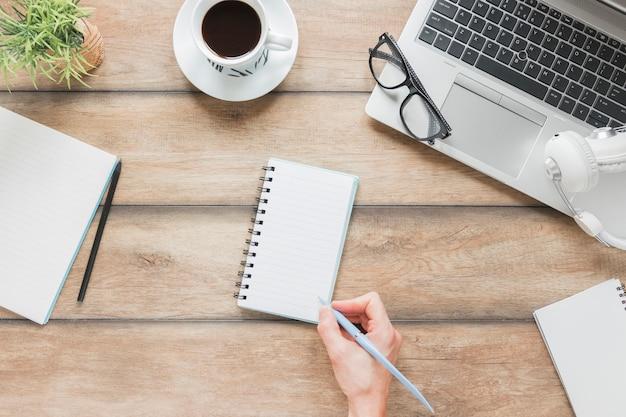 Persona sin rostro escribiendo en cuaderno cerca de papelería y portátil en la mesa Foto gratis
