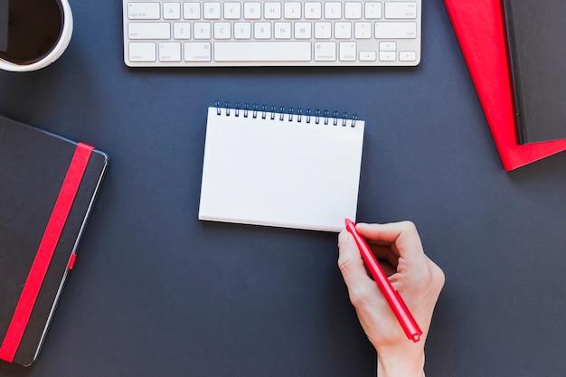 Persona sin rostro escribiendo en el cuaderno cerca de la taza de café y el teclado Foto gratis