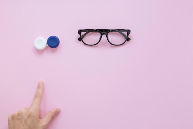 Persona señalando anteojos y lentes de contacto Foto gratis
