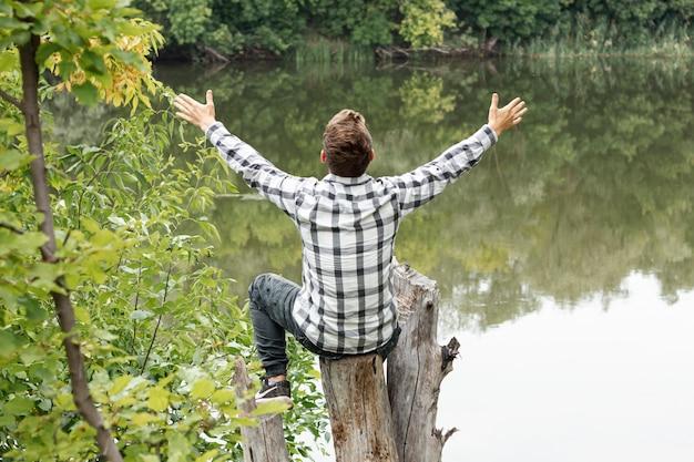 Persona sentada en un árbol con las manos abiertas Foto gratis