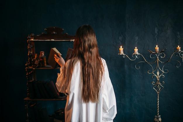 Persona de sexo femenino en camisa blanca pone viejo libro de hechizos en el estante, vista posterior, velas. magia oscura, ocultismo y exorcismo, brujería Foto Premium