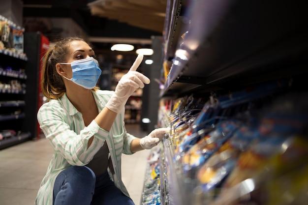 Persona de sexo femenino con máscara y guantes comprando alimentos en el supermercado Foto gratis