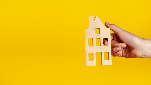 Persona sosteniendo una casa de madera con espacio de copia Foto Premium