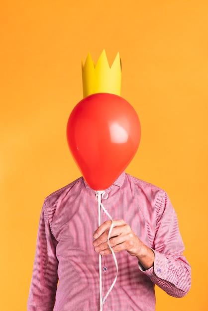 Persona sosteniendo un globo sobre fondo naranja Foto gratis