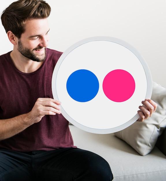 Persona sosteniendo un ícono de flickr Foto gratis