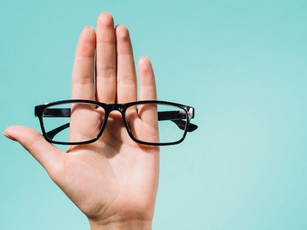 Persona sosteniendo un par de anteojos Foto Premium