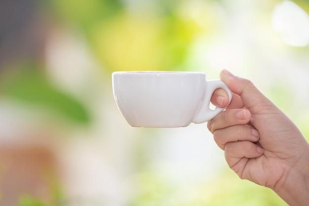 La persona está sosteniendo una taza de café con leche Foto gratis