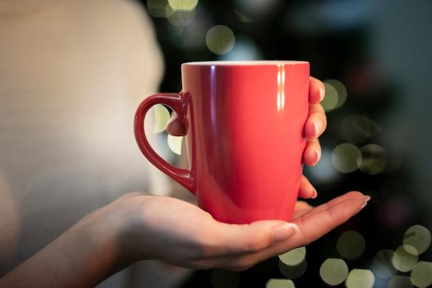 Persona sosteniendo una taza con fondo de navidad Foto gratis