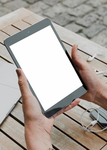 Persona sujetando tableta maqueta al aire libre Foto gratis
