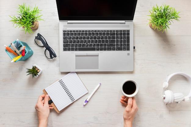 Una persona con una taza de café y diario en el escritorio de madera con una computadora portátil abierta Foto gratis