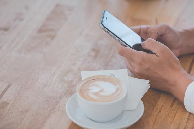 Persona con un teléfono inteligente y un café. Foto gratis