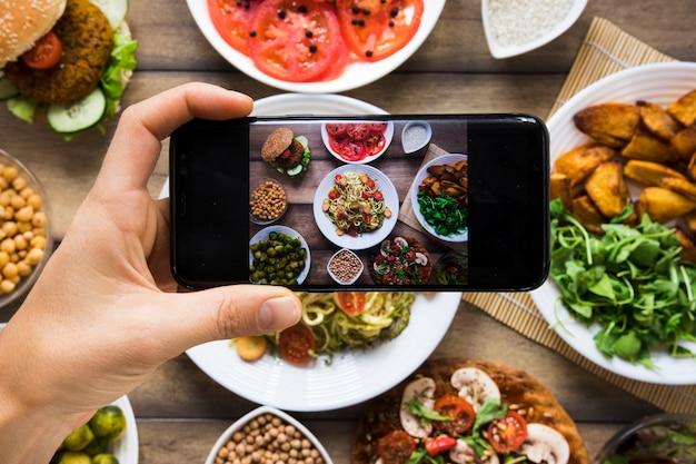 Persona tomando una foto de diferentes platos veganos Foto gratis