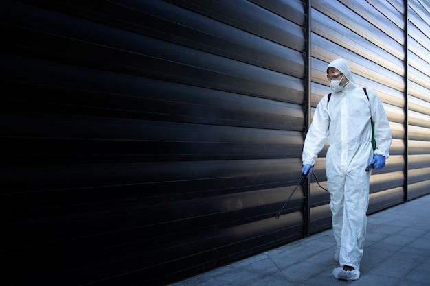 Persona con traje blanco de protección química realizando desinfección y control de plagas y rociando veneno para matar insectos y roedores Foto gratis